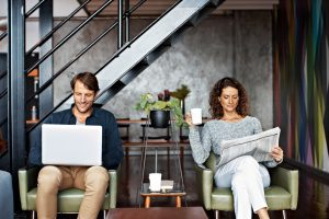 Shot of a content mature couple sitting in their living room reading the newspaper and using a laptop